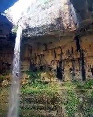 Cet homme plonge du haut de cette falaise le long d'une chute d'eau magnifique... vertigineux