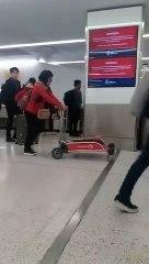 Elle pousse le chariot à bagages dans le mauvais sens... Pas très futée